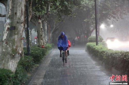 12日上午8点许,南京市区突降暴雨,市民在暴雨中艰难前行。