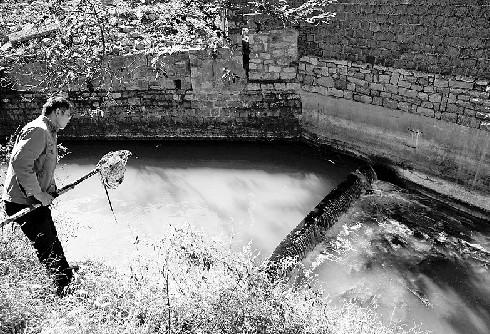 水从卧虎山水库老出水孔放出,村民怀疑是这些看上去有些污浊的水污染了他们祖祖辈辈饮用的地下水。