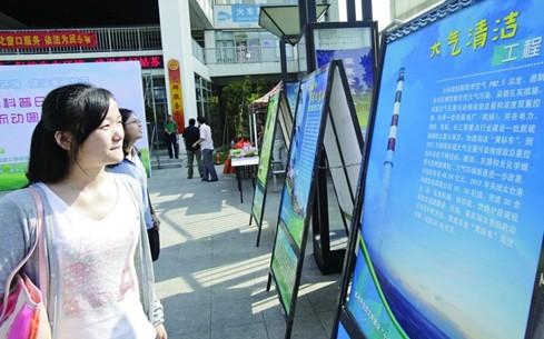 科技学院学生在参观保护大气层知识的宣传展牌